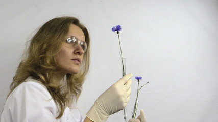 Researcher woman watch at flasks with genetically modified plant