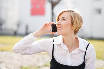 Blonde businesswoman in formal wear calling outdoor