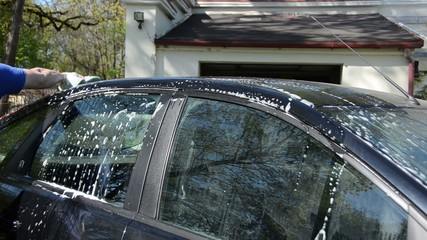 Man with sponge wash automobile car roof in garden yard