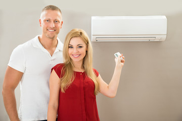 Couple With Remote Control Air Conditioner