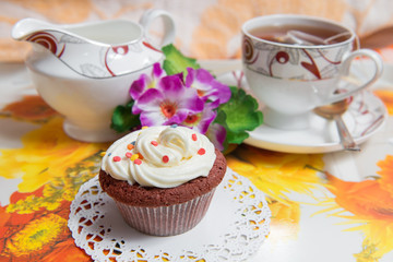Sweet cake with cup of tea and flowers