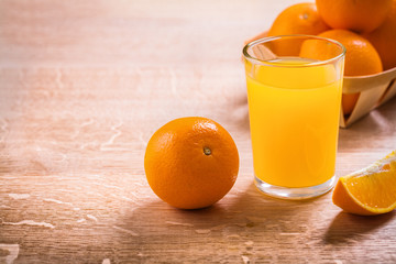 horizontal version glass with juice and oranges on wooden board