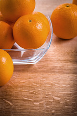 orange fruits in glass square bowl on wooden desk