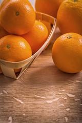 oranges in wicker basket on wooden board