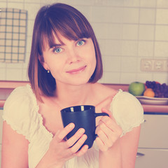 Young woman, enjoying a cup of coffee in her home.