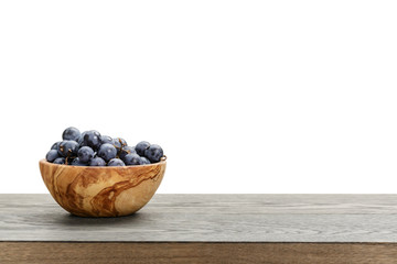 isabella grapes in wood bowl on table, border compostition