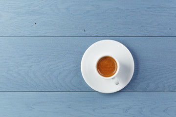 cup of fresh espresso on vintage blue table from above