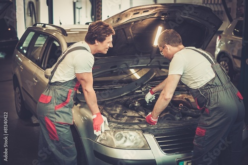 Two mechanics fixing car in a workshop - 81340422