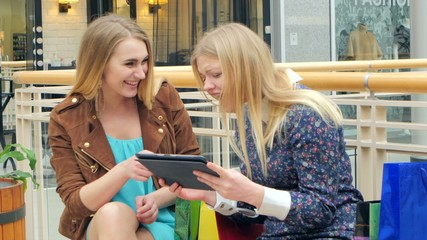 Shopping Women with Digital Tablet bench on the trading floor