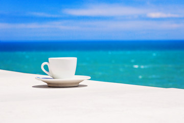 A cup of coffee on table with sea at the background