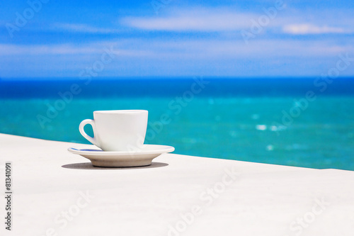 A cup of coffee on table with sea at the background - 81341091