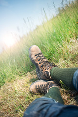Man lying down resting in the grass with trekking boots