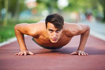 Young man exercising outdoor, doing push-ups