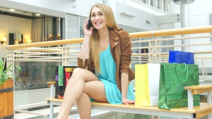 Beautiful girl sitting bench in mall, talking on the phone