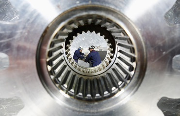 engineers working, seen through a giant cogwheel