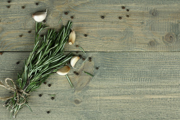 Closeup of garlic,rosemary and peppercorns on wooden background