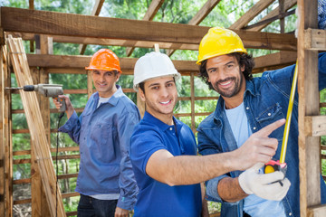 Happy Construction Workers Working In Wooden Cabin