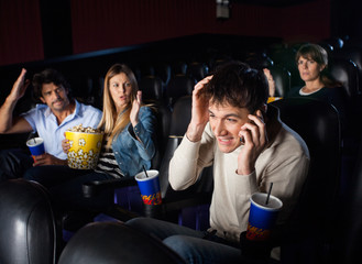 Spectators Shouting Man Using Mobilephone In Theater
