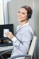Portrait Of Young Female Customer Service Executive Holding Coff