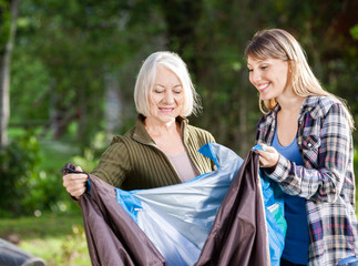 Smiling Mother And Daughter Assembling Tent In Park