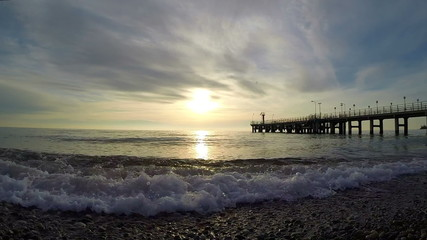 Evening surf in Black Sea at sunset and the pier in Sochi