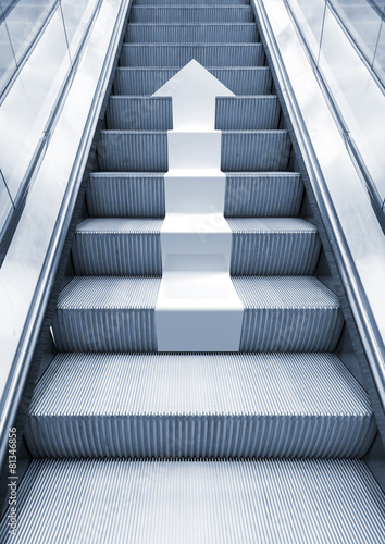 Deurstickers Trappen Shining metal escalator with white arrow moving up