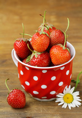 ripe organic strawberries on a wooden background