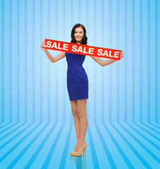 happy young woman in dress with red sale sign