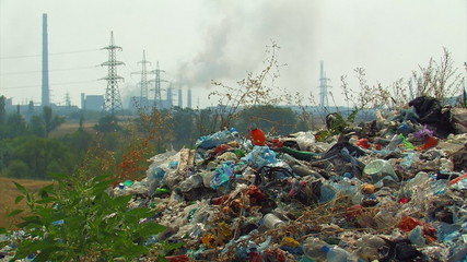 Landfill on the background of smoking chimneys and power lines.