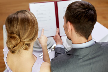close up of happy couple with menu at restaurant