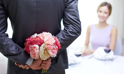 close up of man hiding flowers behind from woman