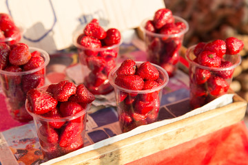 strawberry in plastic cups at street market