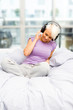 Blonde smiling woman is listening to music with headphones in th