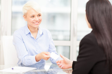 Businesswoman giving her business card to another businesswoman