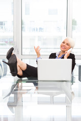 Blonde businesswoman is phoning in the office with legs on the d