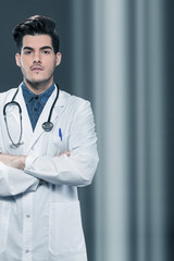 Serious doctor with crossed hands over grey background