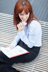 Top shot of businesswoman with charts sitting outside on a metal
