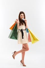 Happy woman holds a credit card and shopping bags