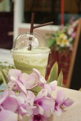 Iced green tea with flowers in the garden.