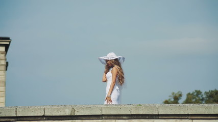 High beautiful girl in a white dress with hat walking on the