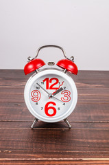 Alarm clock on wooden board background