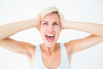Angry blonde screaming and holding her head