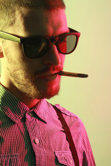 Portrait of handsome casual stylish young man smoking cigarette