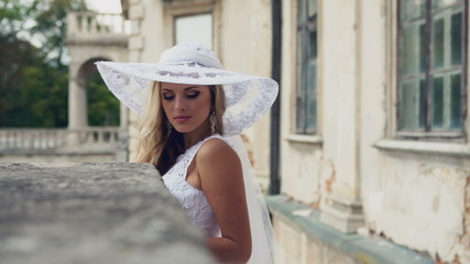 Chic aristocratic woman in retro style white dress and hat. Long
