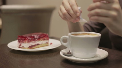 Girl drinks coffee with a cake