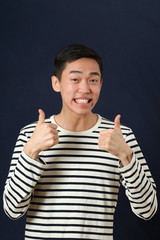 Smiling young Asian man giving the thumbs up signs and looking a