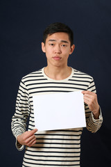 Young Asian man showing white copy space page and looking at cam