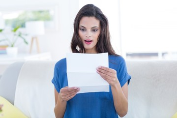 Surprised beautiful brunette reading letter