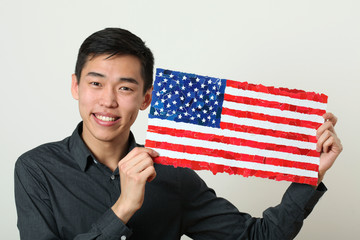 Young Asian student showing US national flag and looking at came