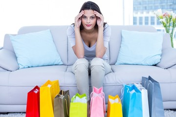 Worried brunette sitting on the couch with shopping bag